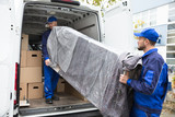 Two Delivery Men Unloading Furniture From Vehicle - 187877737