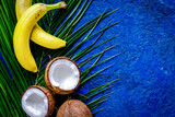 Appetizing cocount, banana and palm branch on blue table backgro - 187879512
