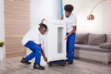 Two Male Movers Placing The White Cabinet On Wheel - 187881338