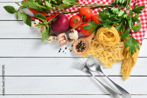Foto Murales Pasta spaghetti, farfalle, linguine with vegetables and spices on white wooden table