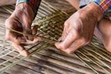 Old man hands manually weaving bamboo.