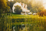 rural view, blurred background. pond and house in the distance at sunset - 187899101