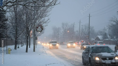 Foto op Plexiglas New York TAXI Snowfall in the city with cars, street lamps and traffic light