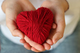 Children's hands hold a heart of red thread for knitting. Valentine's Day . - 187908575