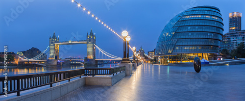 Poster Panoramafoto s LONDON, GREAT BRITAIN - SEPTEMBER 19, 2017 - The panorama of the Tower bridge, promenade with the the modern Town Hall building at dusk.