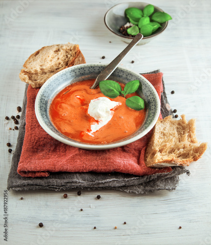 Foto Murales Fresh Tomato soup in a bowl with tomatoes and basil on a white kitchen table