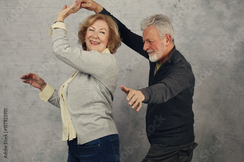 Fototapeta Happy stylish elderly couple dancing and laughing. Vintage image