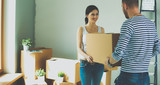 Happy young couple unpacking or packing boxes and moving into a new home - 187934740