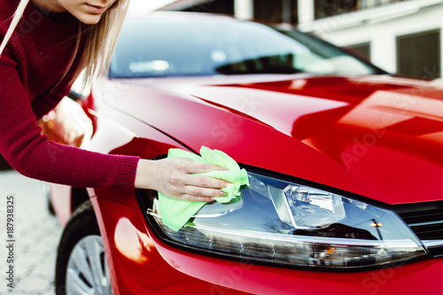 Foto Murales Young woman cleaning car with microfiber cloth, car detailing (or valeting) concept