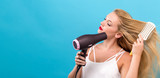Beautiful woman holding a hairdryer on a blue background