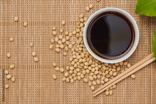 Soy sauce and soy bean with chopsticks on wooden table
