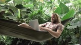 Man working on laptop while sitting on hammock, exotic background - 187946177