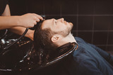 Barber shop. Hairdresser man washes client head in barbershop