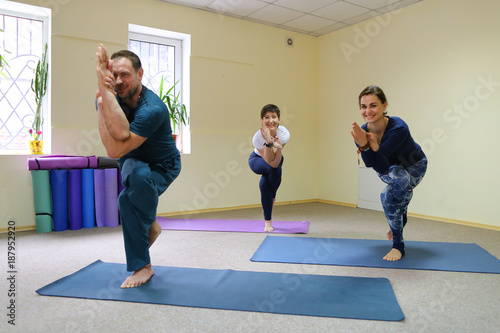 Obraz na płótnie Young woman yoga trainer teaches the boy and girl to do the exer