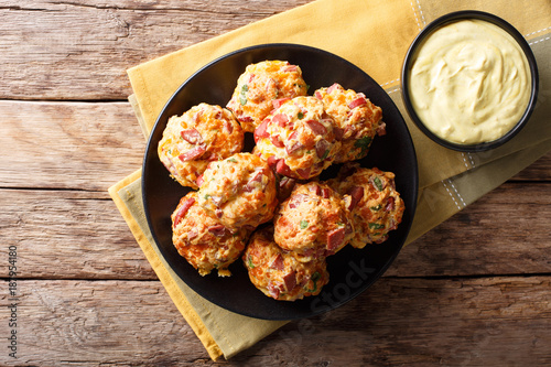 Fotobehang Bol Freshly baked sausage balls with cheese cheddar on a plate and mustard sauce close-up. horizontal top view