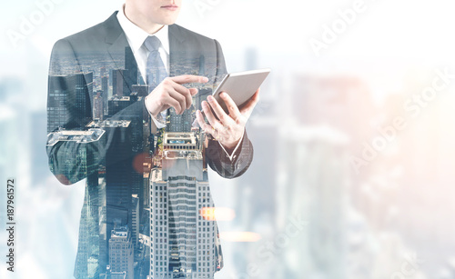 Handsome businessman with a digital tablet, city