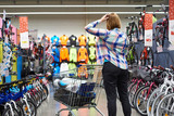 Woman chooses the goods in sports store - 187961796