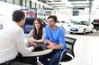 Verkaufsgespräch im Autohandel - Verkäufer berät junges Paar - im Hintergrund neue PKW´s im Showroom // Sales talk in a car dealership - salesman advises young couple