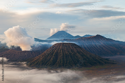 Fotobehang Bleke violet Bromo volcano and mount Batok (Gunung Batok) with cloudy smoke in early morning, East Java, Indonesia