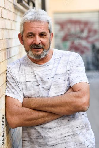 Foto Murales Mature man smiling looking at camera in urban background