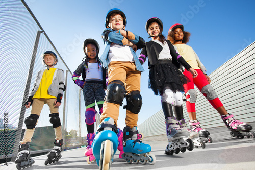 Papiers peints Kiev Boy in rollerblades standing with friends outdoors