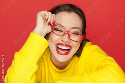 beautiful happy woman with red glasses on red background