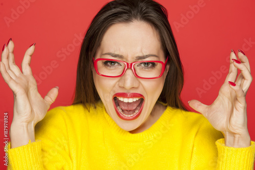 beautiful angry woman with red glasses on red background
