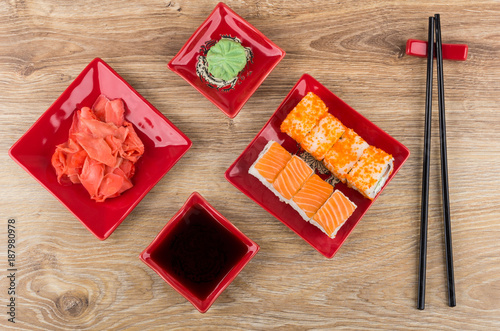 Foto op Canvas Sushi bar Rolls with flying fish roe, salmon, soy sauce, wasabi, chopsticks