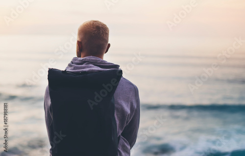 Foto Murales Hipster hiker tourist with backpack looking of seascape sunset on background blue sea, guy enjoying ocean horizon, blurred panoramic sunrise, traveler relax holiday concept, trip vacation