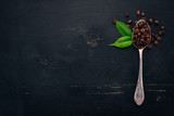 Coffee beans. On a spoon lie on a wooden background. Top view. Copy space.