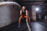 Front view of Attractive young fit and toned sportswoman working out with battle ropes - 187995589