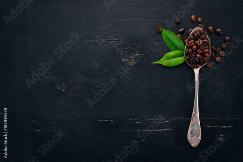 Coffee beans. On a spoon lie on a wooden background. Top view. Copy space. - 187995578