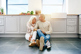 Affectionate senior couple sitting together on their kitchen floor - 187997393