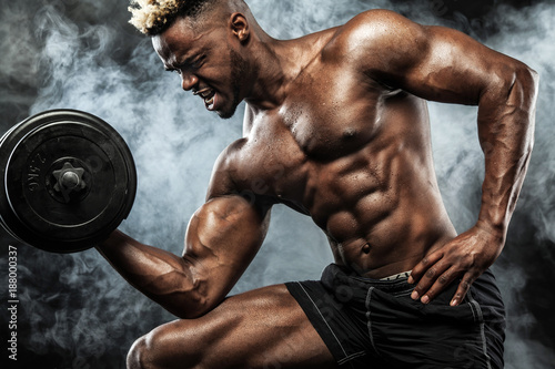 Fridge magnet Muscular young fitness sports man workout with dumbbell in fitness gym