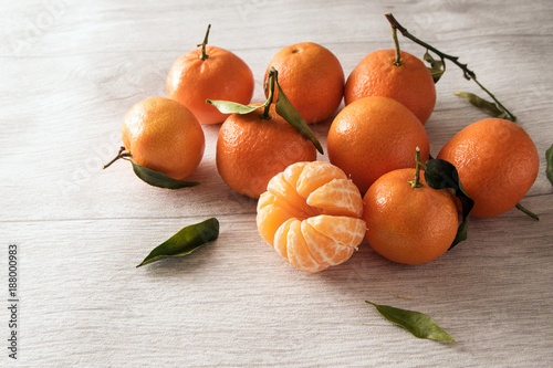 Foto Murales group of clementines with leaves, whole and peeled on a light gray wooden background with copy space
