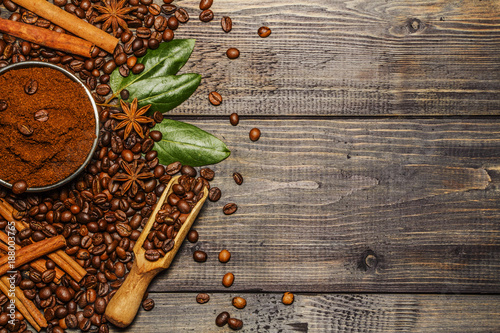 Deurstickers Koffiebonen Coffee beans, ground, cinnamon, anise on a wooden background. View from above.
