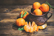 tangerines in clay crockery on a wooden table..