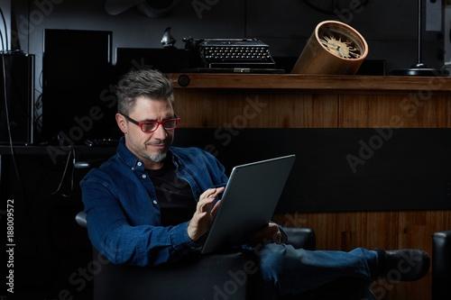 Foto Murales Older man sitting in dark room using tablet