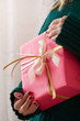 Closeup of Christmas, birthday or any other celebration gift wrapped in red paper and decorated with ribbons in girl's hands.
