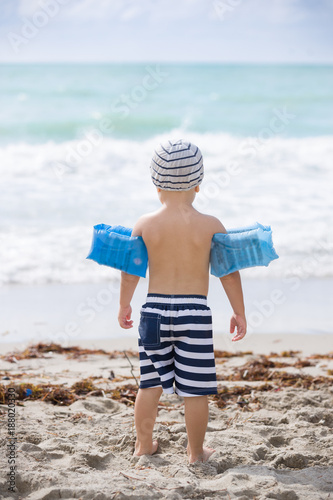 Back view on cute toddler boy wearing safety inflatable armbands standing on the beach ready to jump into ocean or sea. Safety first. Vacations.