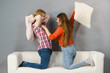 Man and woman having pillow fight