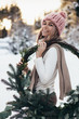 Blonde young lady in pink knitted hat with christmas wreath in winter snowy forest