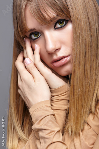 Aluminium Kapsalon Portrait of blonde young woman. Female with green eyes and long hair. Girl dressed in beige dress on gray background.