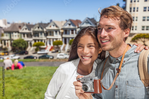 Foto Murales San Francisco Painted Ladies houses people tourists on America summer trip holidays taking photos, Young multiethnic couple asian woman, caucasian man.