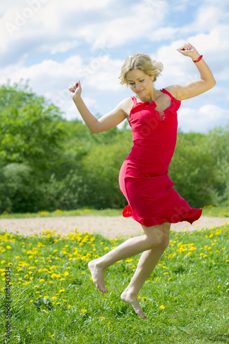Beautiful girl in red dress jumps on the grass.