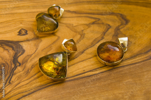 Tuinposter Edelsteen three pendants with blue amber on the wooden board