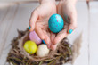 Close-up of of a woman hand is holding cyan easter egg above the nest with colorful Easter eggs on wooden background. Easter concept.