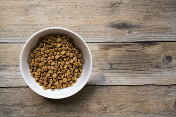 dog food in a bowl on wood table background