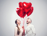 Valentine's Day. Happy joyful couple. Portrait of smiling beauty girl and her handsome boyfriend holding bunch of heart shaped air balloons - 188055198
