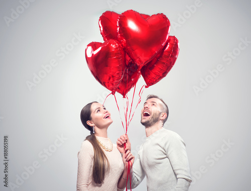 Foto Murales Valentine's Day. Happy joyful couple. Portrait of smiling beauty girl and her handsome boyfriend holding bunch of heart shaped air balloons